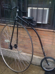 This old school bike is like a unicycle with a training wheel.